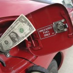 Dollar bill in mouth of gas tank