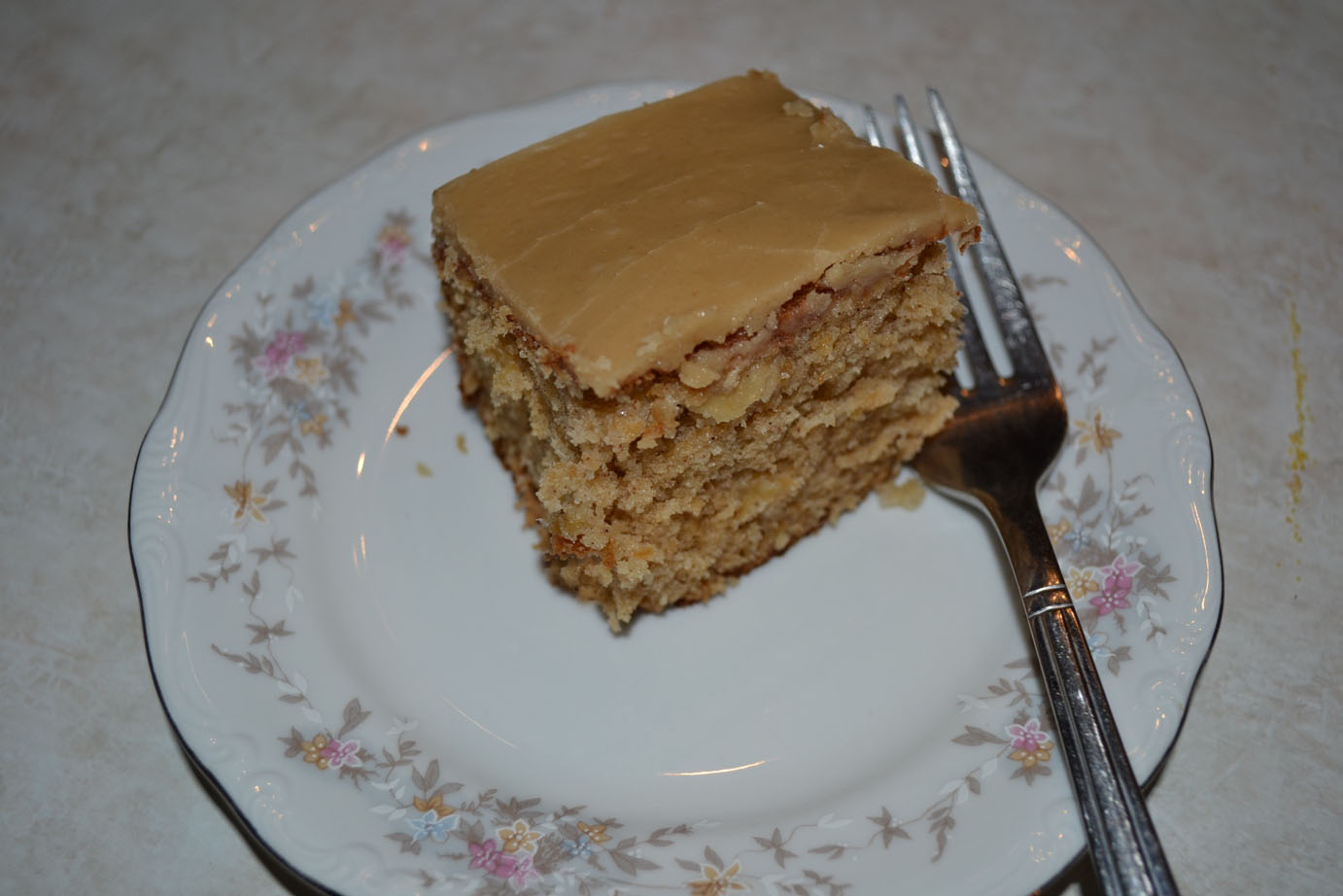 Piece of apple cake with caramel icing on a plate with a fork
