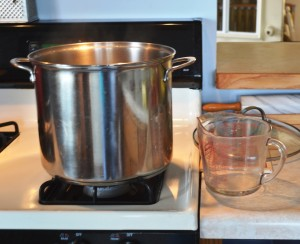 Stockpot on stove with glass measuring cup on counter