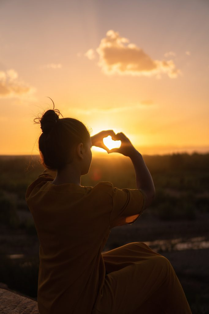 Woman showing heart sign hand - gratitudes in the sunset